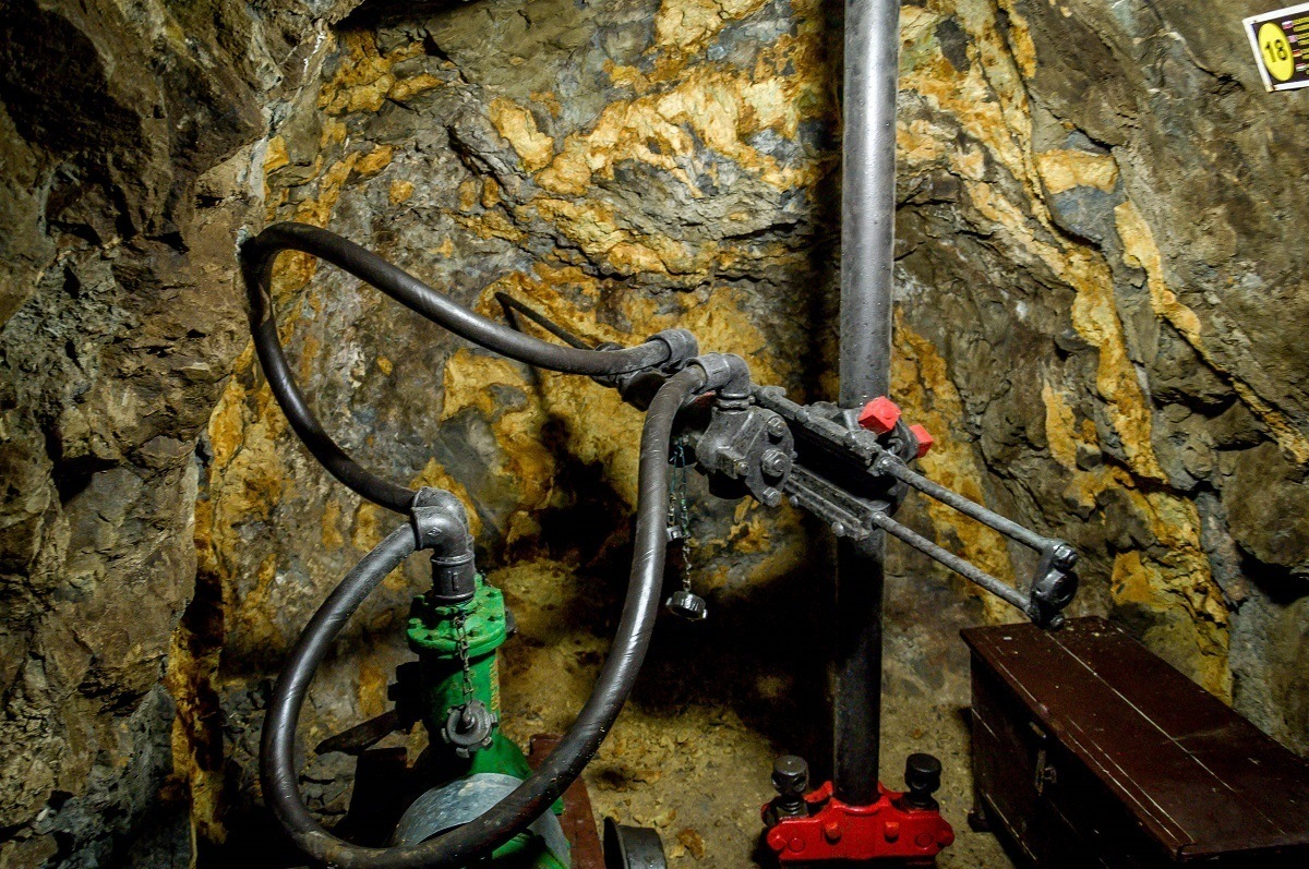 Miners use massive drills with water pumps deep inside the mine