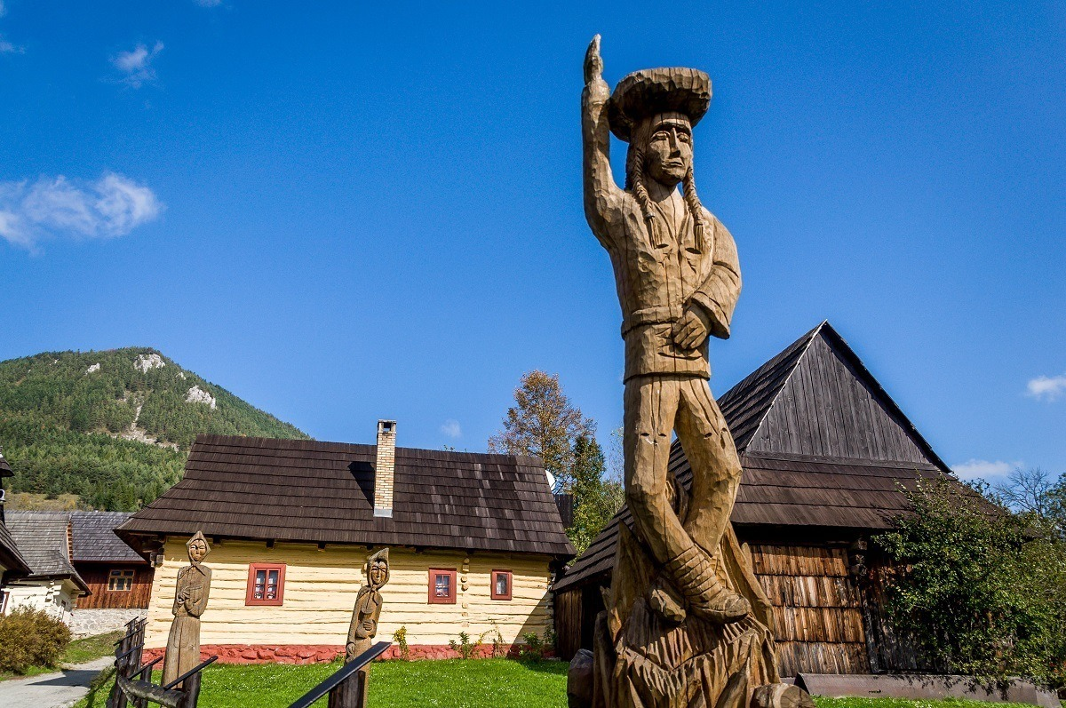 A carved wooden statue welcomes visitors to the rural village of Vlkolinec, Slovakia
