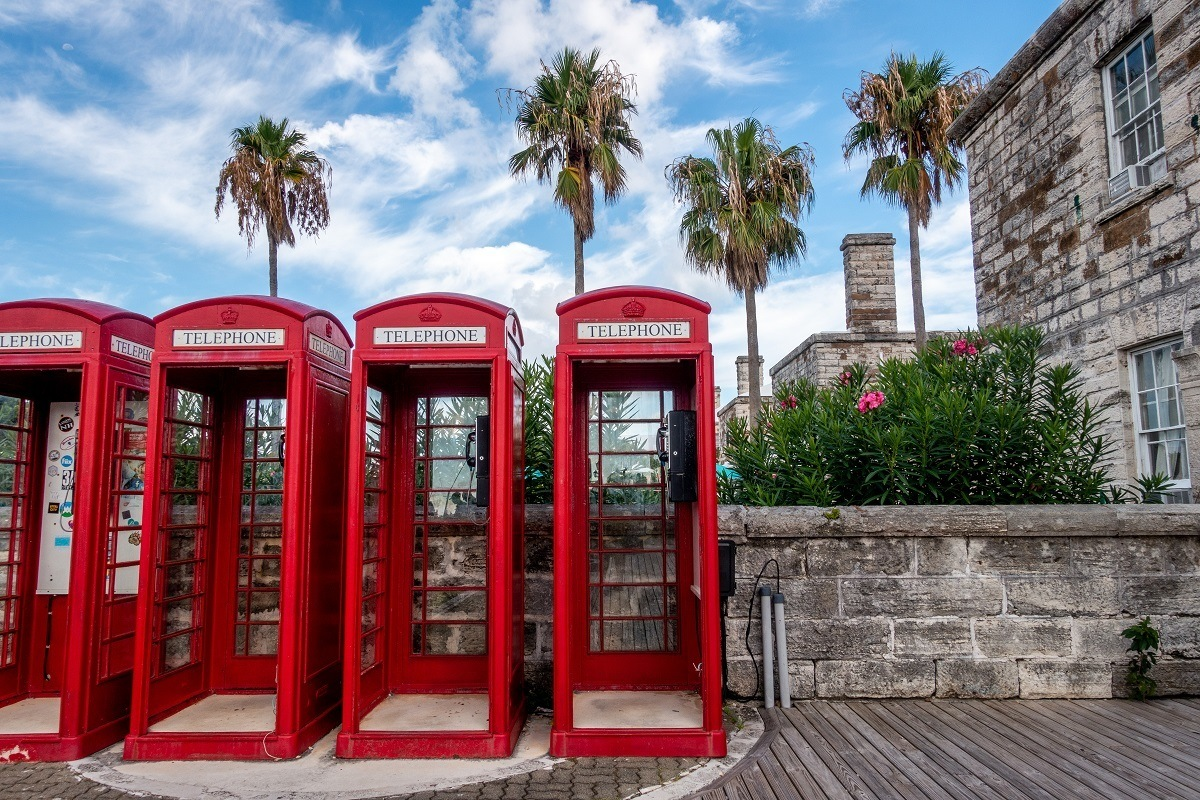 Red British-style phone booths with palm trees