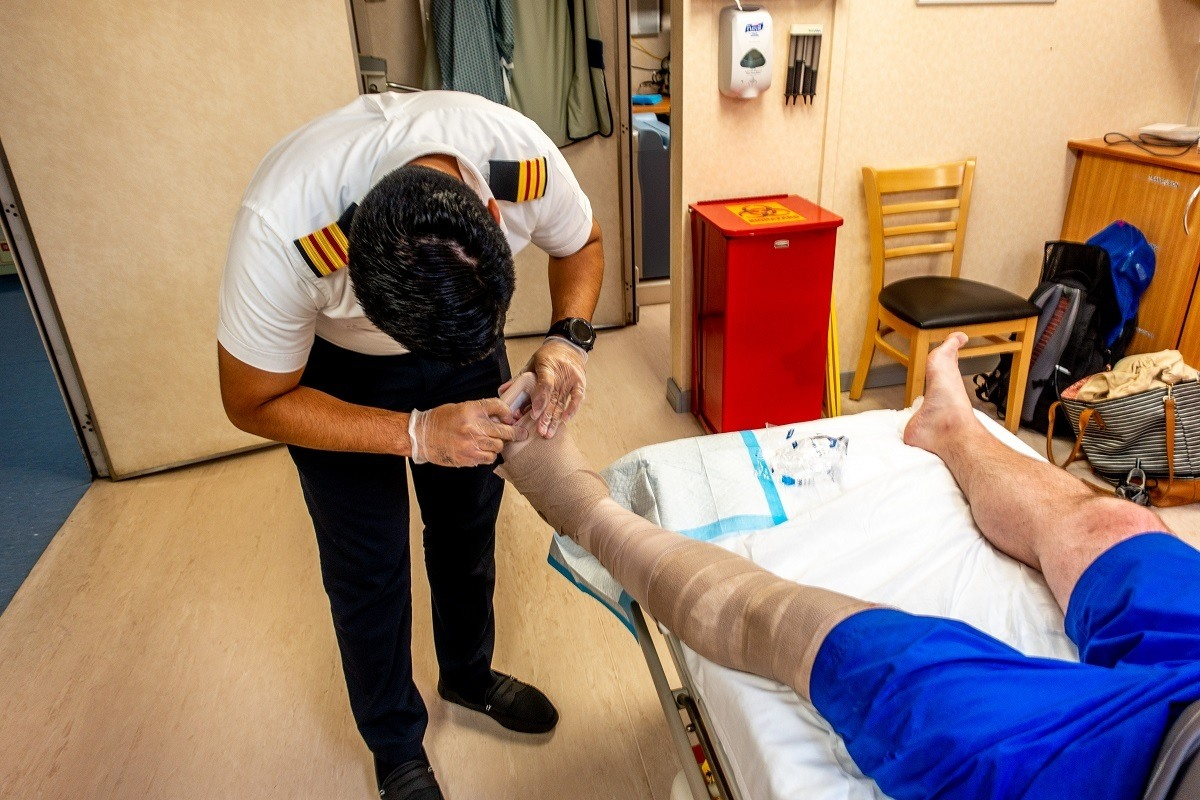 Ship's doctor working on a patient's foot