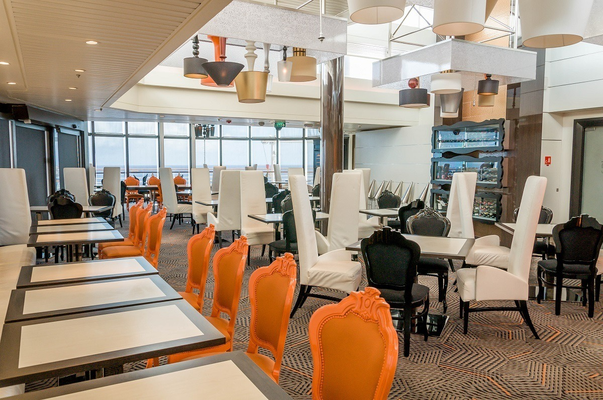 Orange, white, and black chairs at tables in an empty restaurant