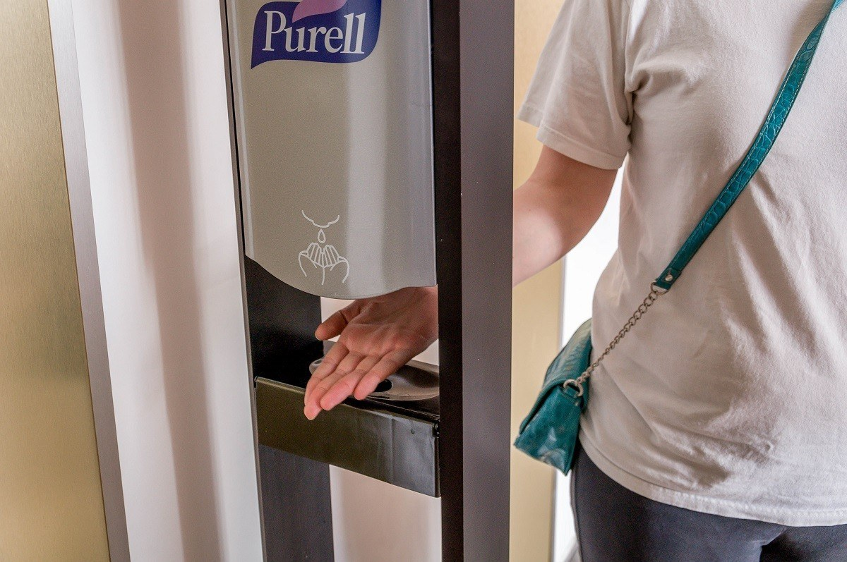 Person with their hand under a Purell hand sanitizer pump