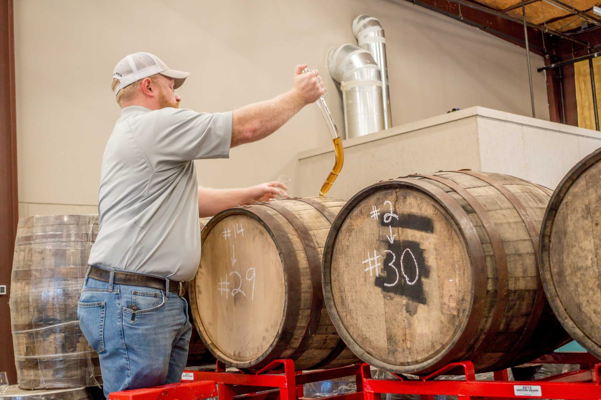 Man opening barrel of whiskey