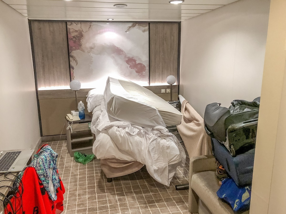 Stateroom with items piled on top of furniture after a flooding