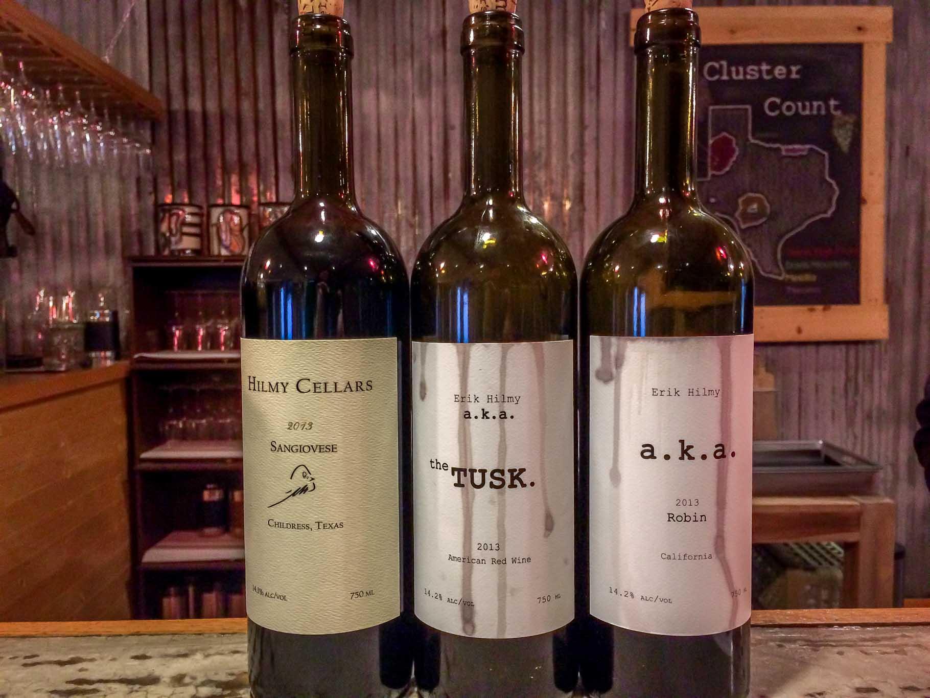 Three wine bottles on a bar