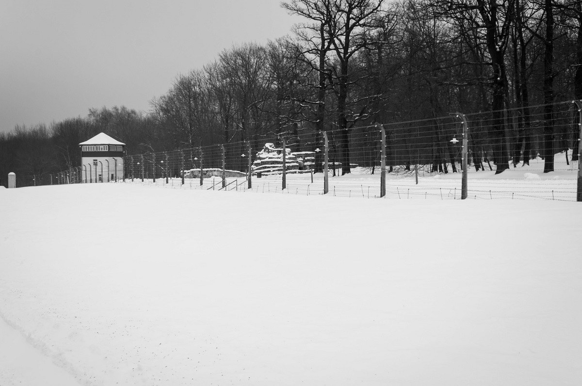 A Nazi concentration camp guard tower and fence in the snow