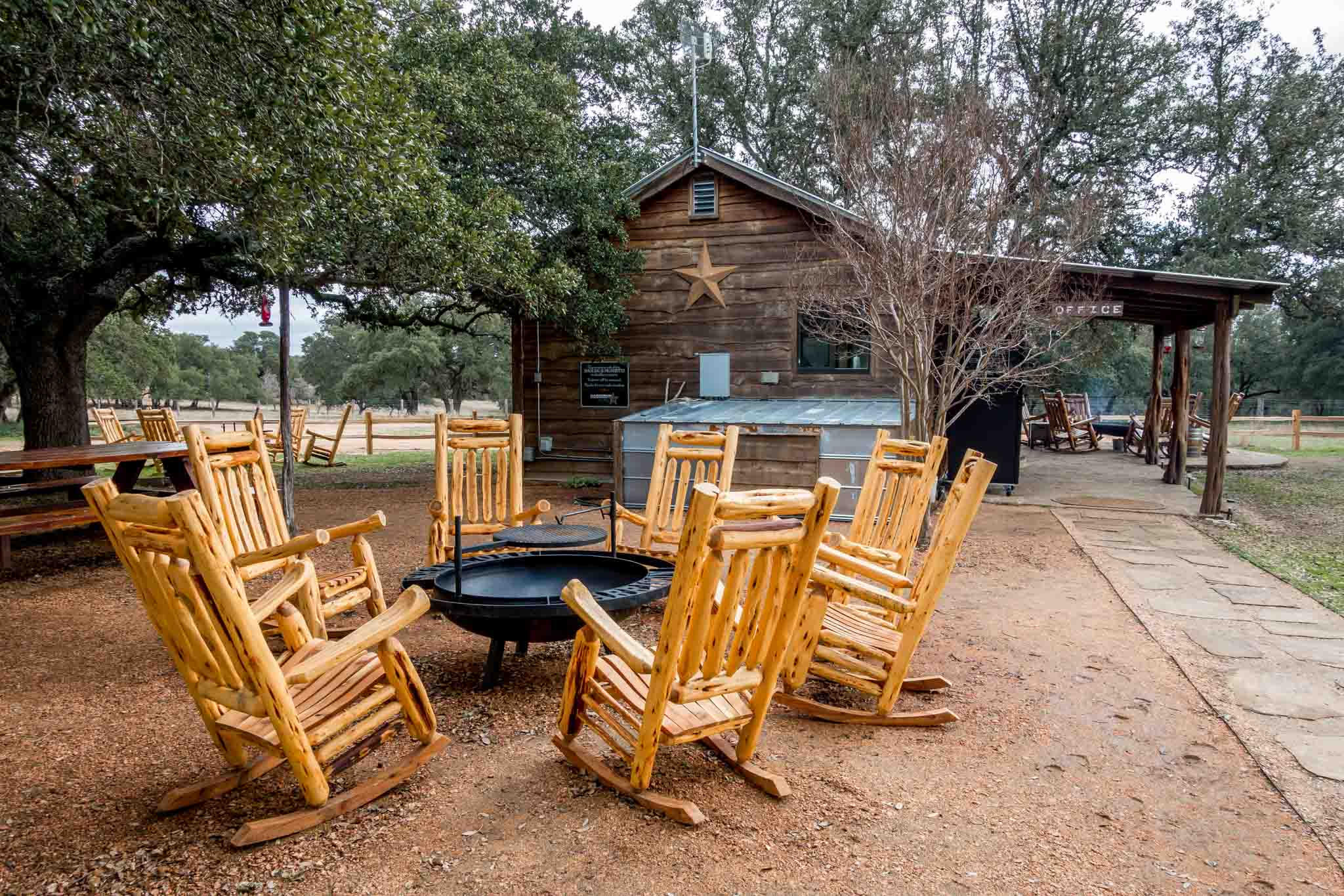 Rocking chairs around fire pit outside a wooden building