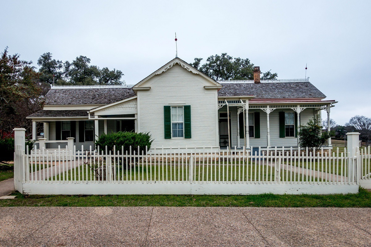 Exterior of a white house with a picket fence