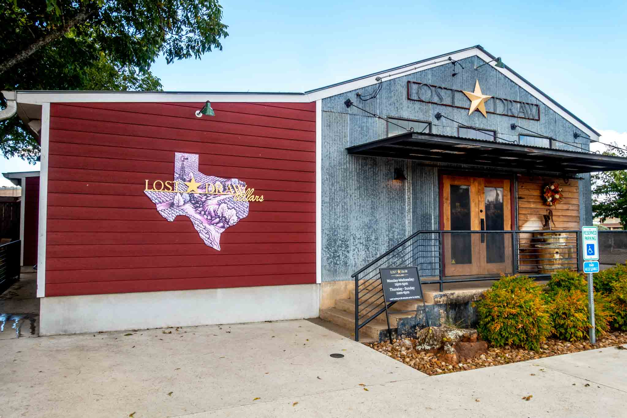 Exterior of Lost Draw tasting room with Texas-shaped logo and signs