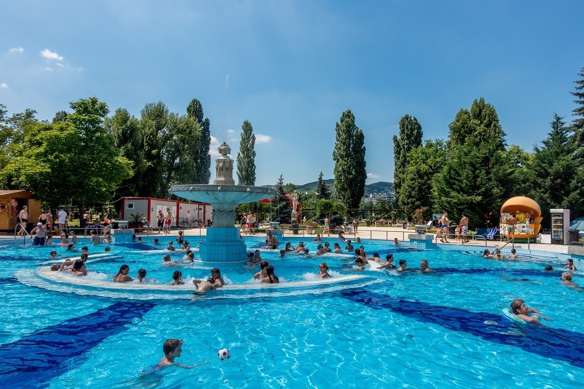 People in a pool with a fountain in the center