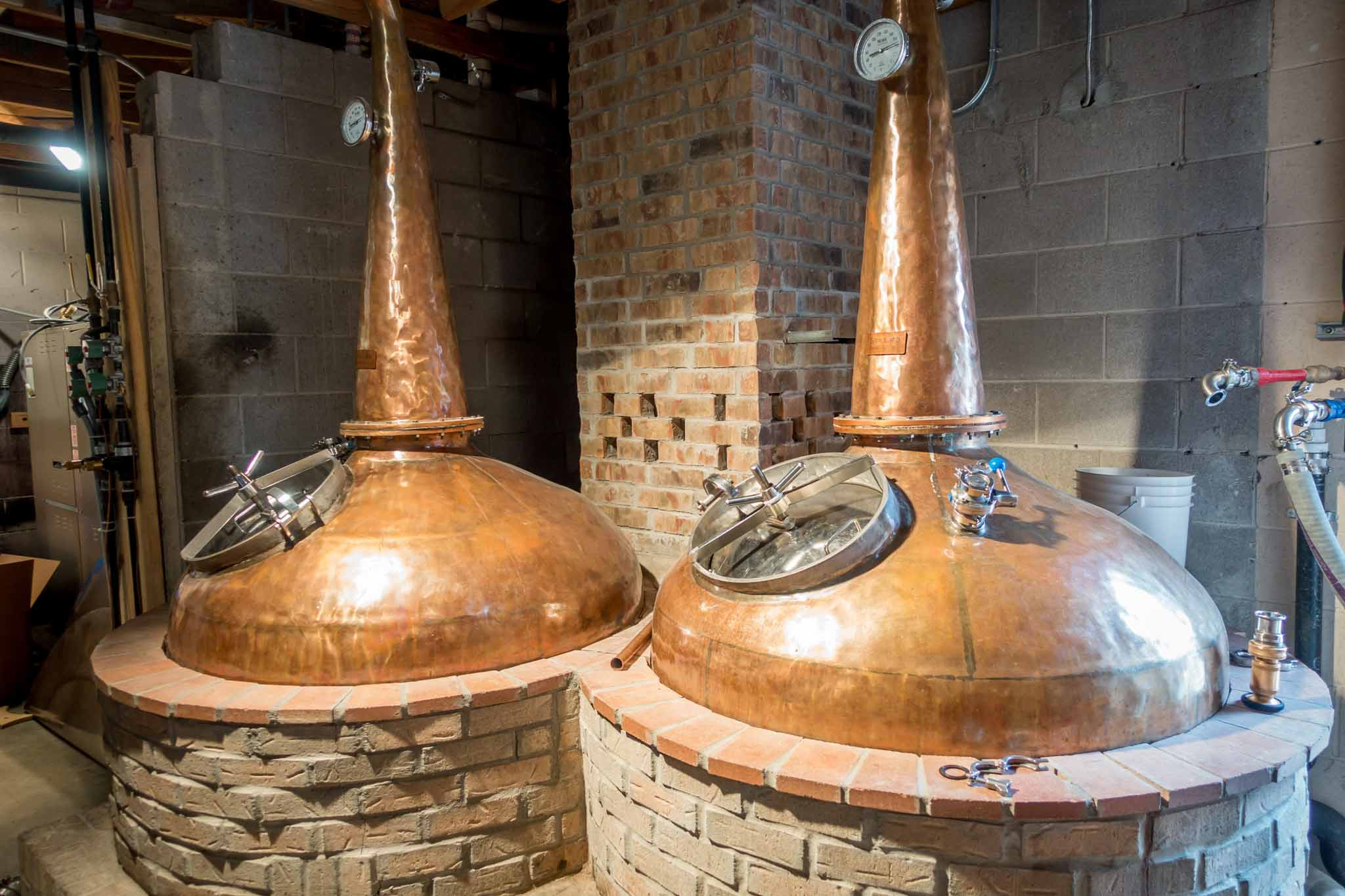 Copper stills surrounded by brick
