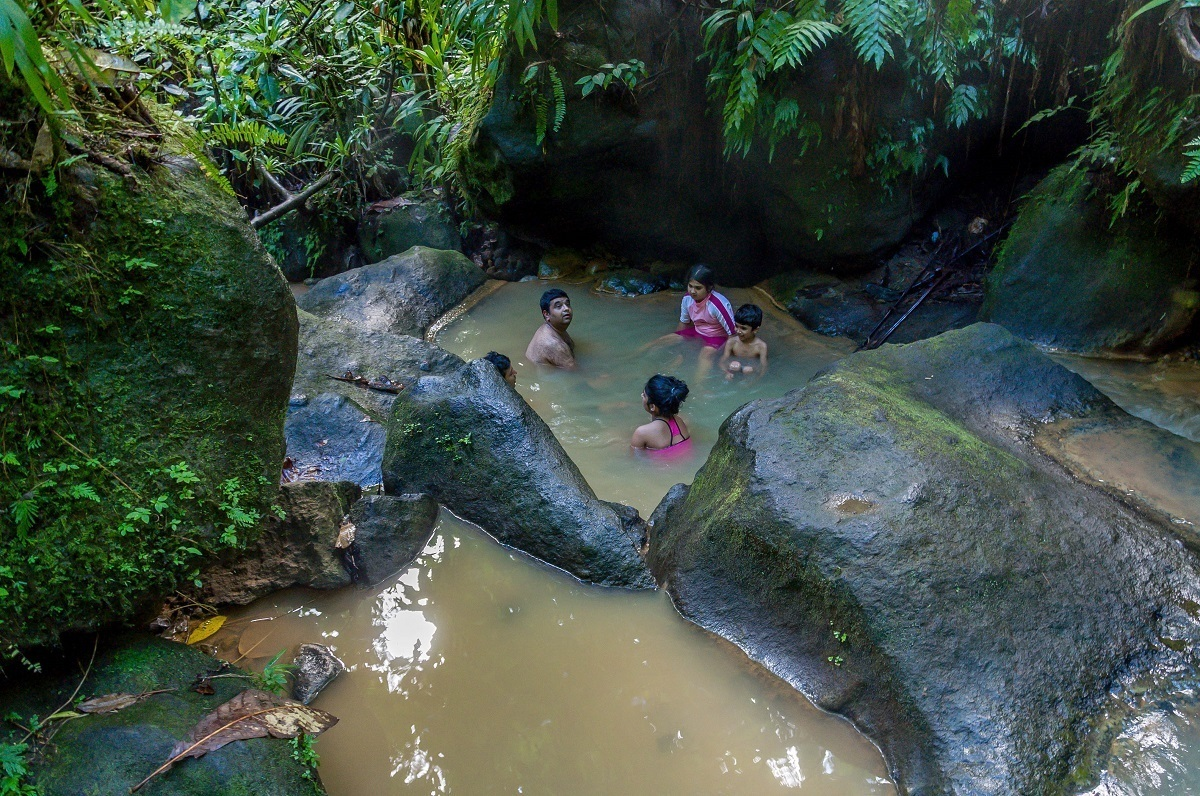 People soaking in a natural hot spring surrounded by trees
