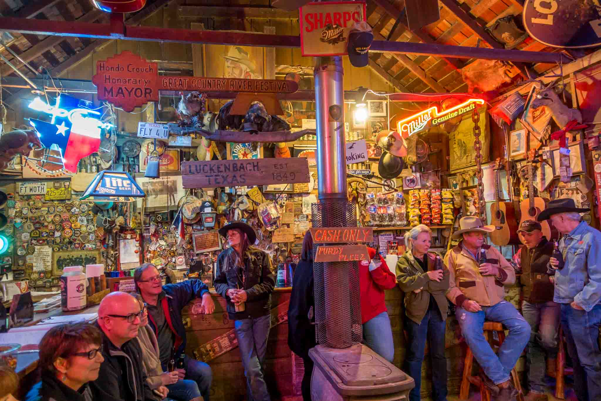 People in a bar filled with signs and memorabilia on the walls