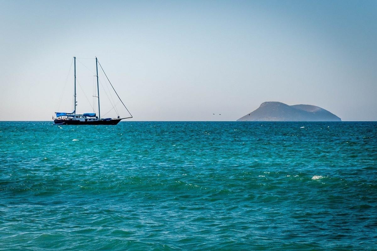 A sailboat on the ocean near an island