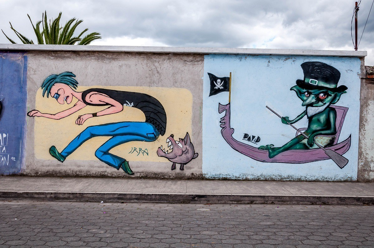 Otavalo street art murals of dog biting boy and pirate in canoe