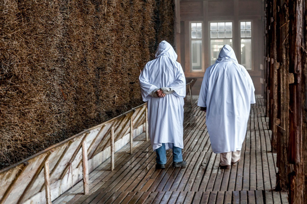 People walking in white hooded robes as they walk along the evaporation walls