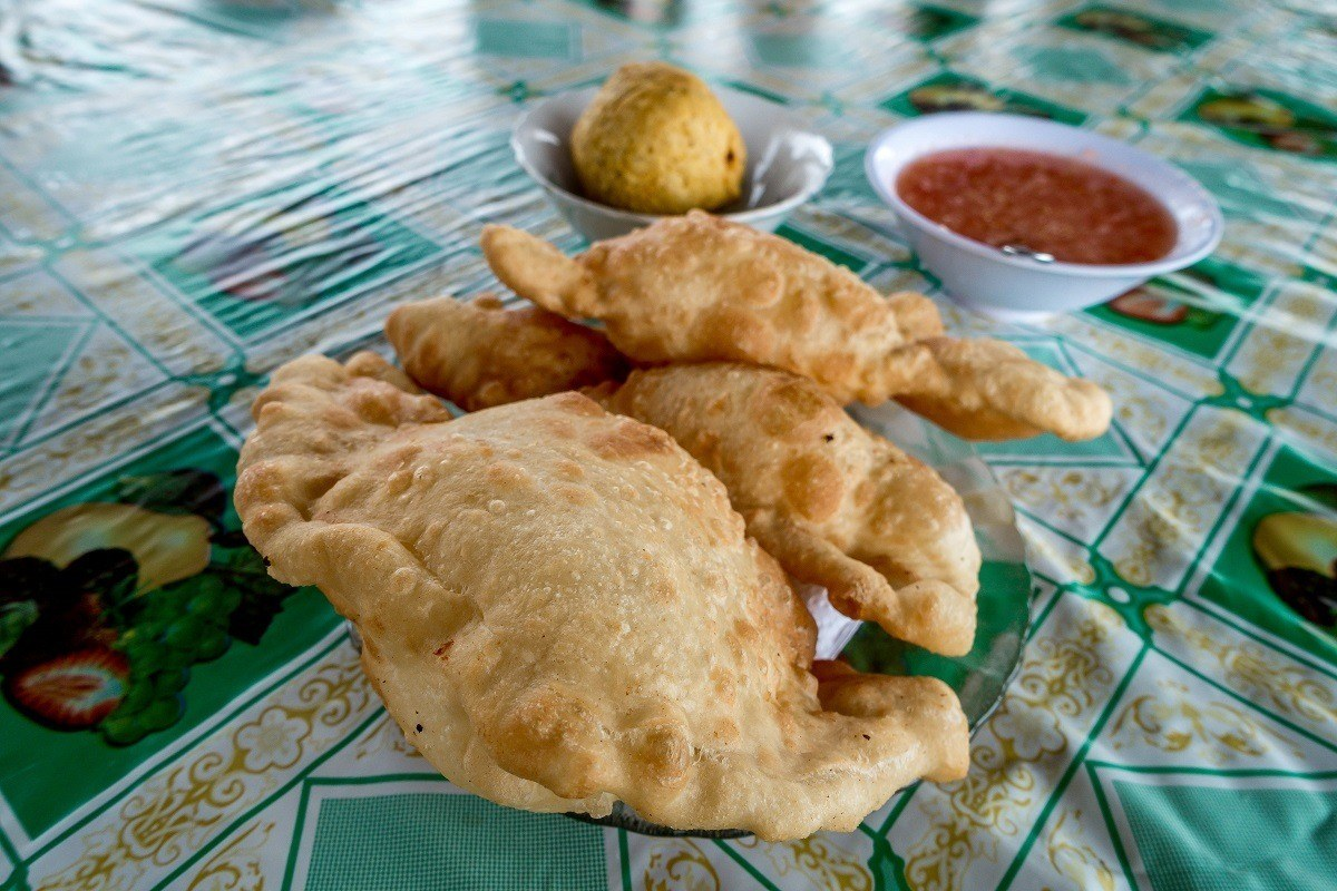 Empanadas wiith aji hot sauce on a table
