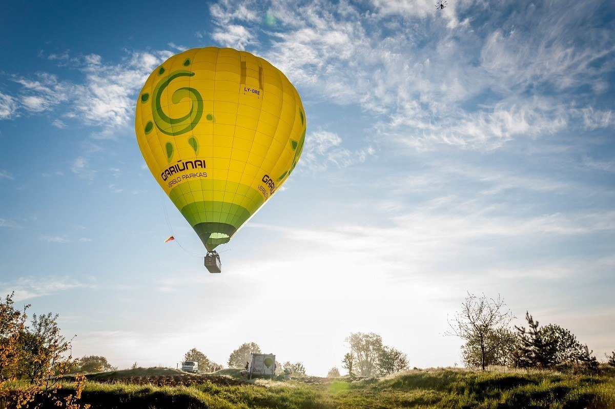 Hot air balloon rising over countryside and Lithuania's Trakai Island Castle