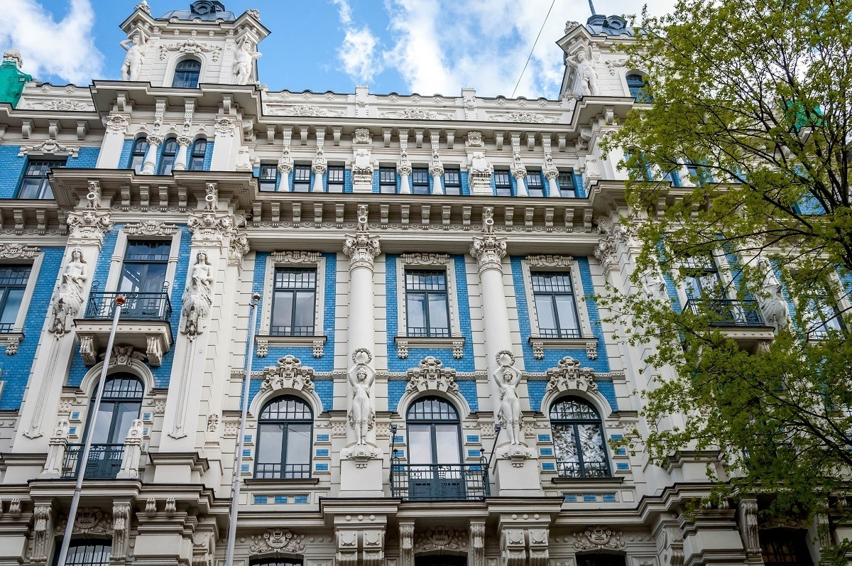 Blue and white Art Nouveau building in Riga with human statues