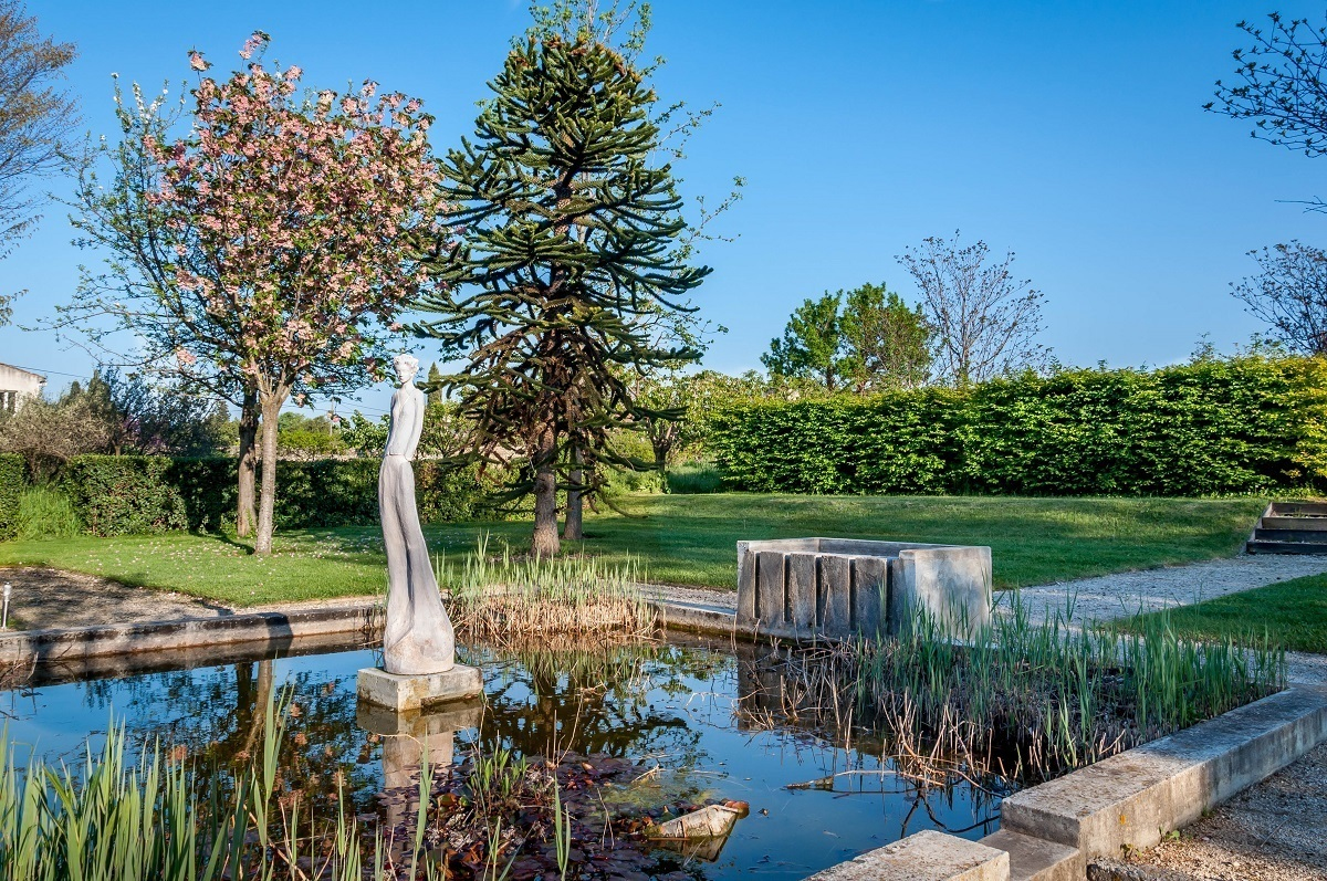 Sculpture in pond surrounded by plants and trees