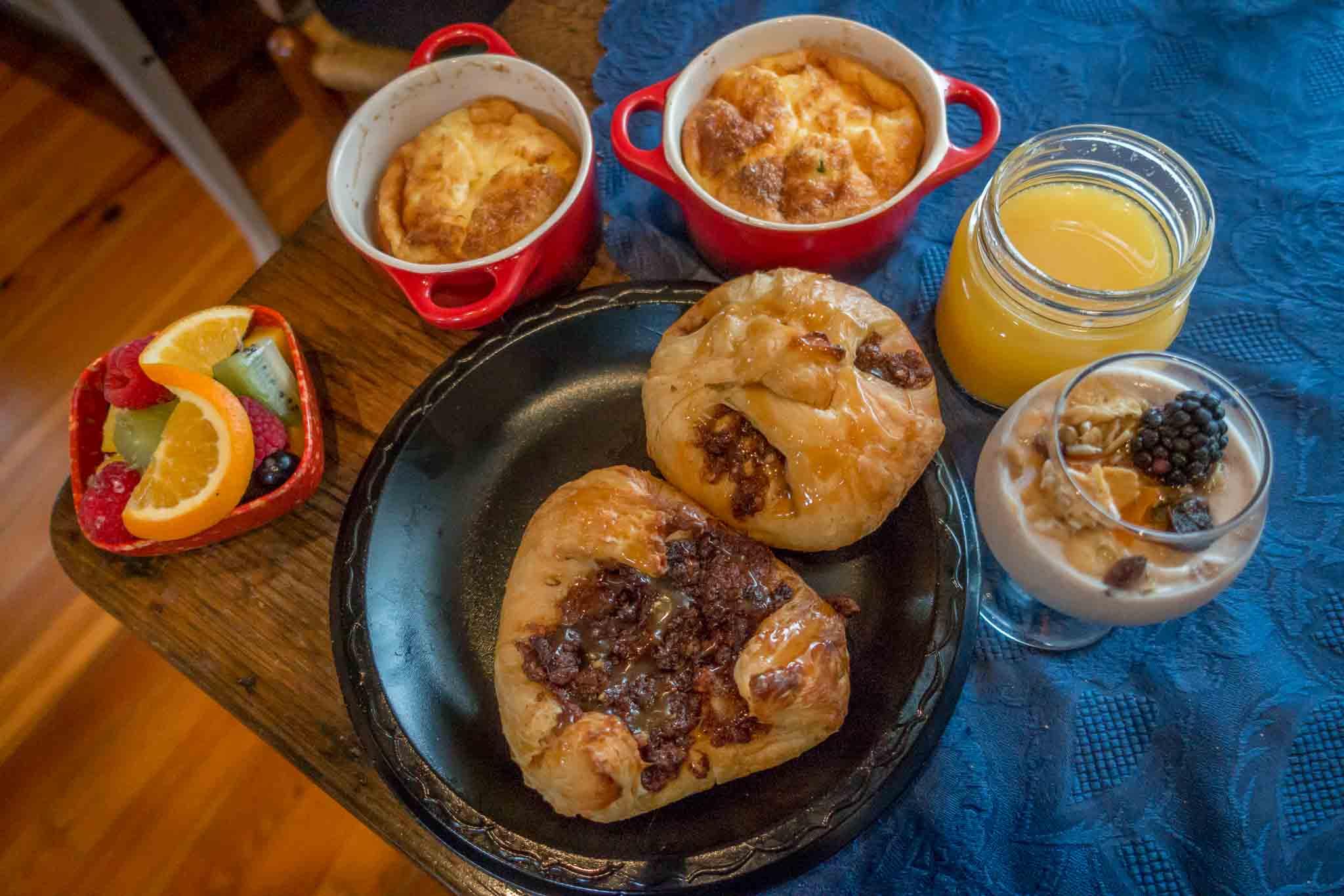 Pastries, souffles, yogurt, fruit, and orange juice on a table