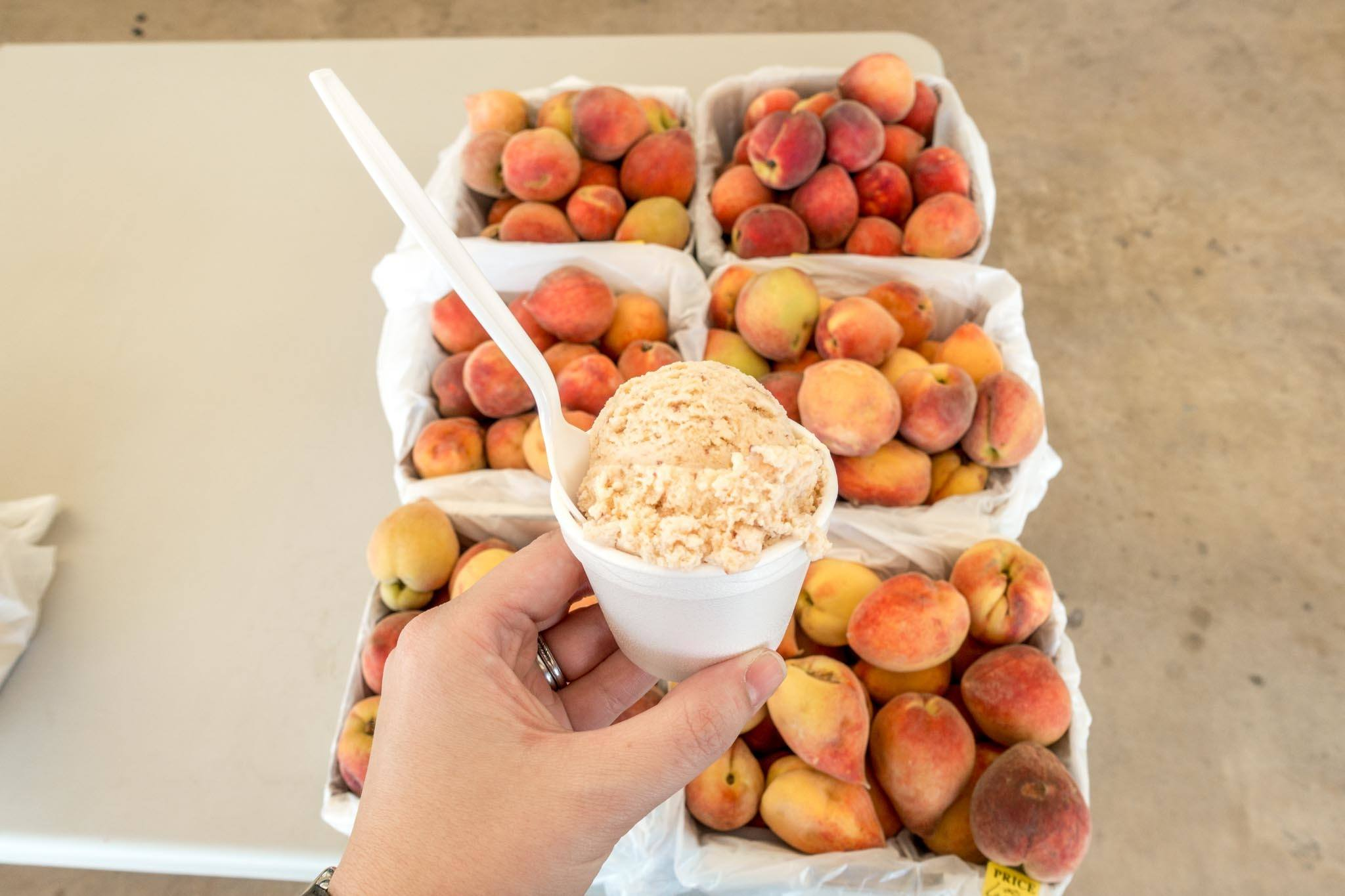 Fresh peaches on a table and peach ice cream in a cup