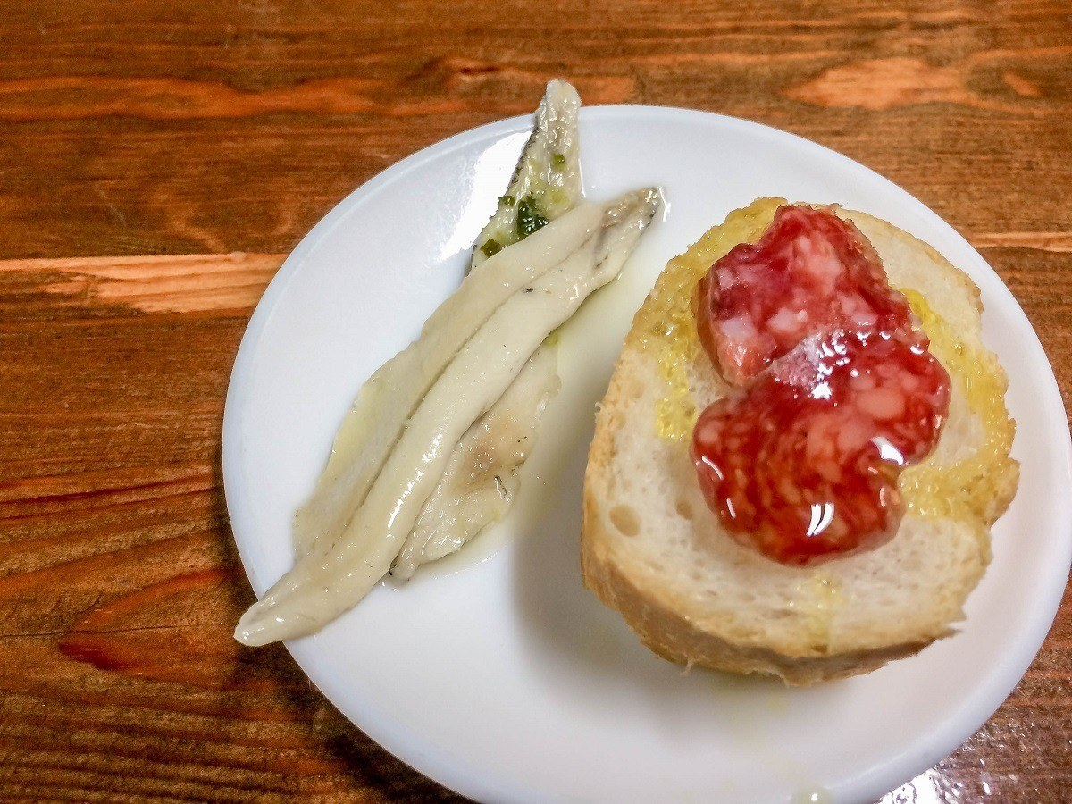 Anchovies and bread with pork sausage on a plate