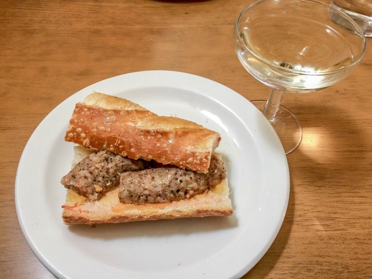 A grilled botifarra (sausage) sandwich with a glass of cava