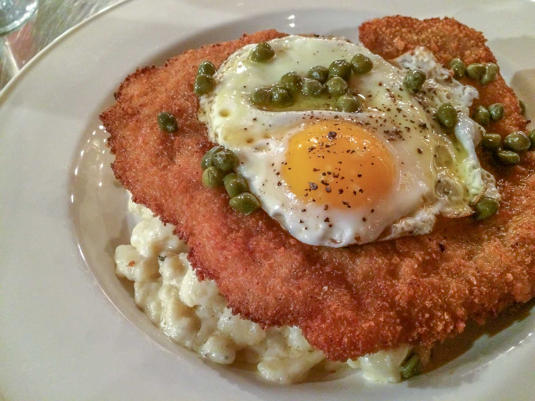 Schnitzel topped with a fried egg and capers on a plate