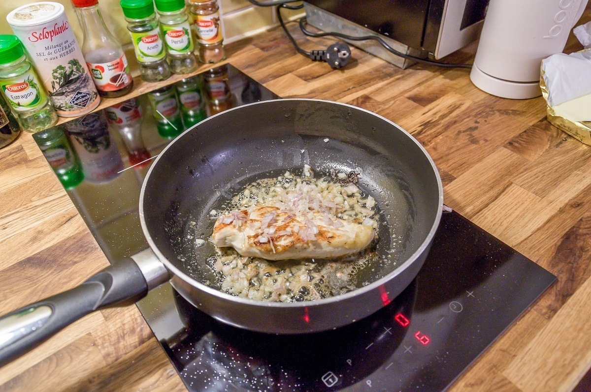 Chicken breast cooking in pan on stove