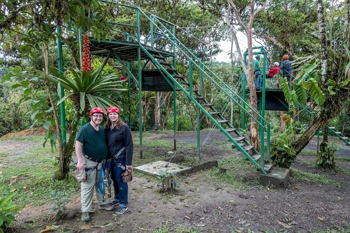People standing near zipline ladders surrounded by vegetation