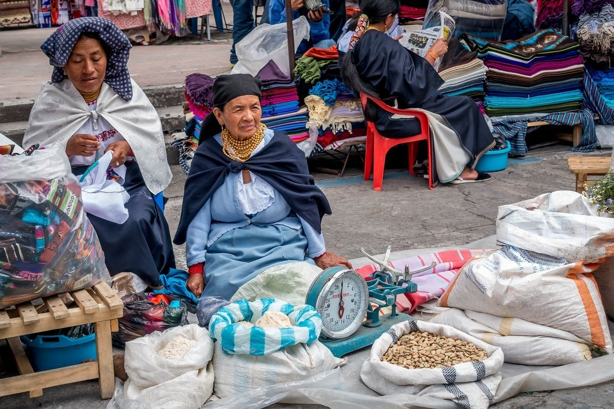 Women traditional Ecuador dress selling beans and lentils in Otavalo