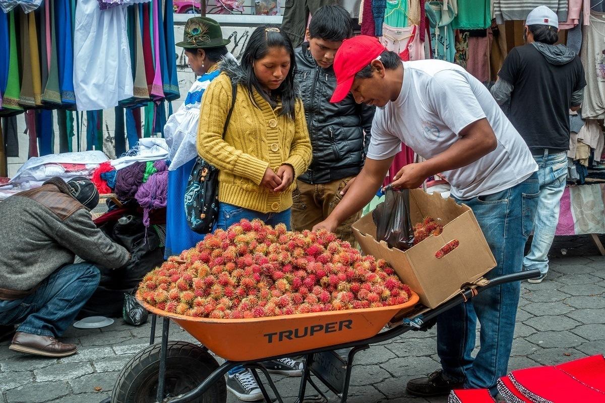 Man selling fruit in the Otavalo market