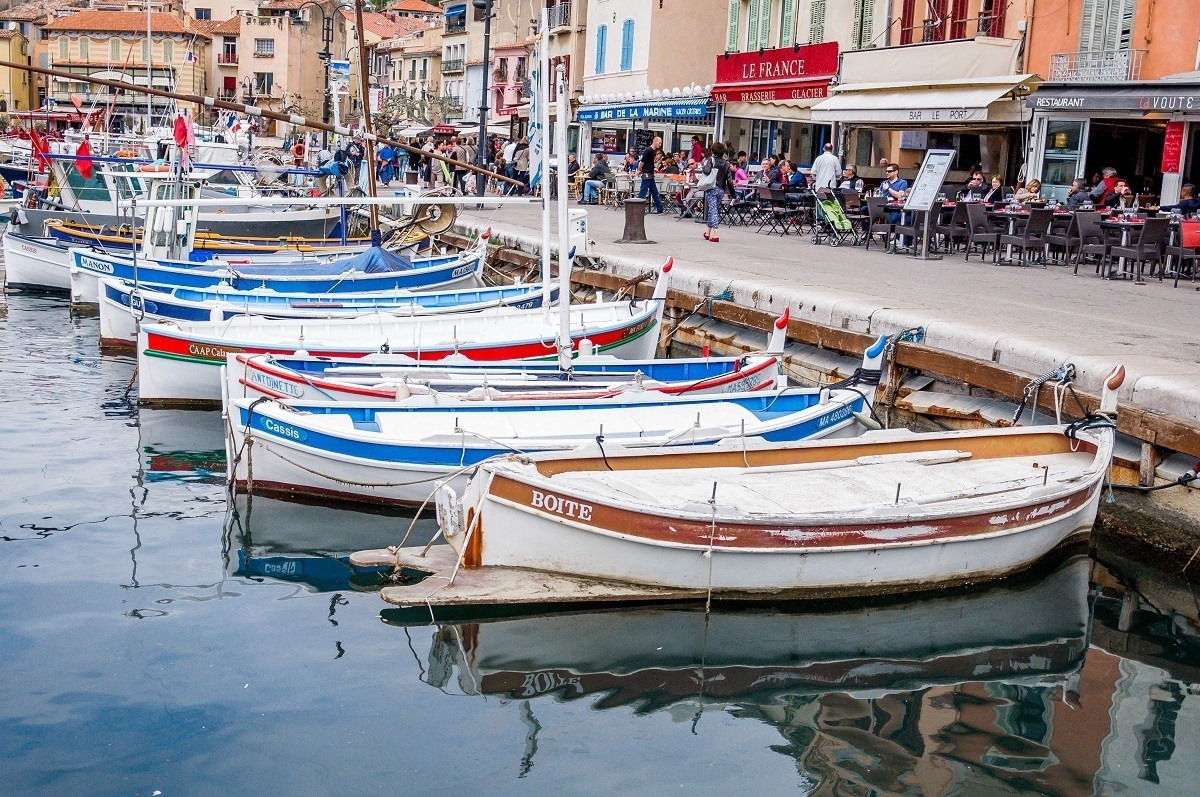 Boats docked in the harbor of Cassis in front of waterfront restaurants