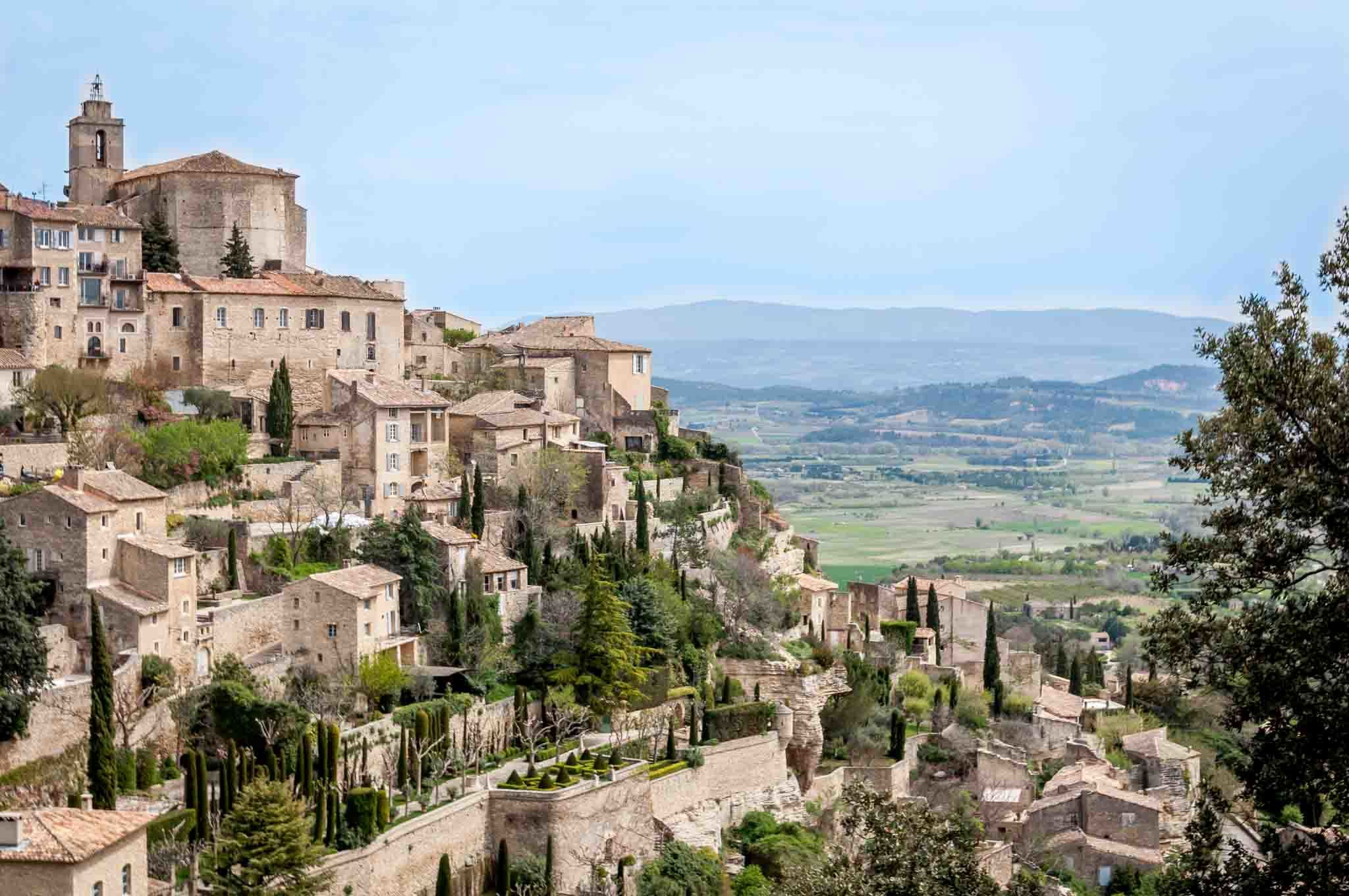 Stone buildings on a mountainside descending to a valley in Gordes