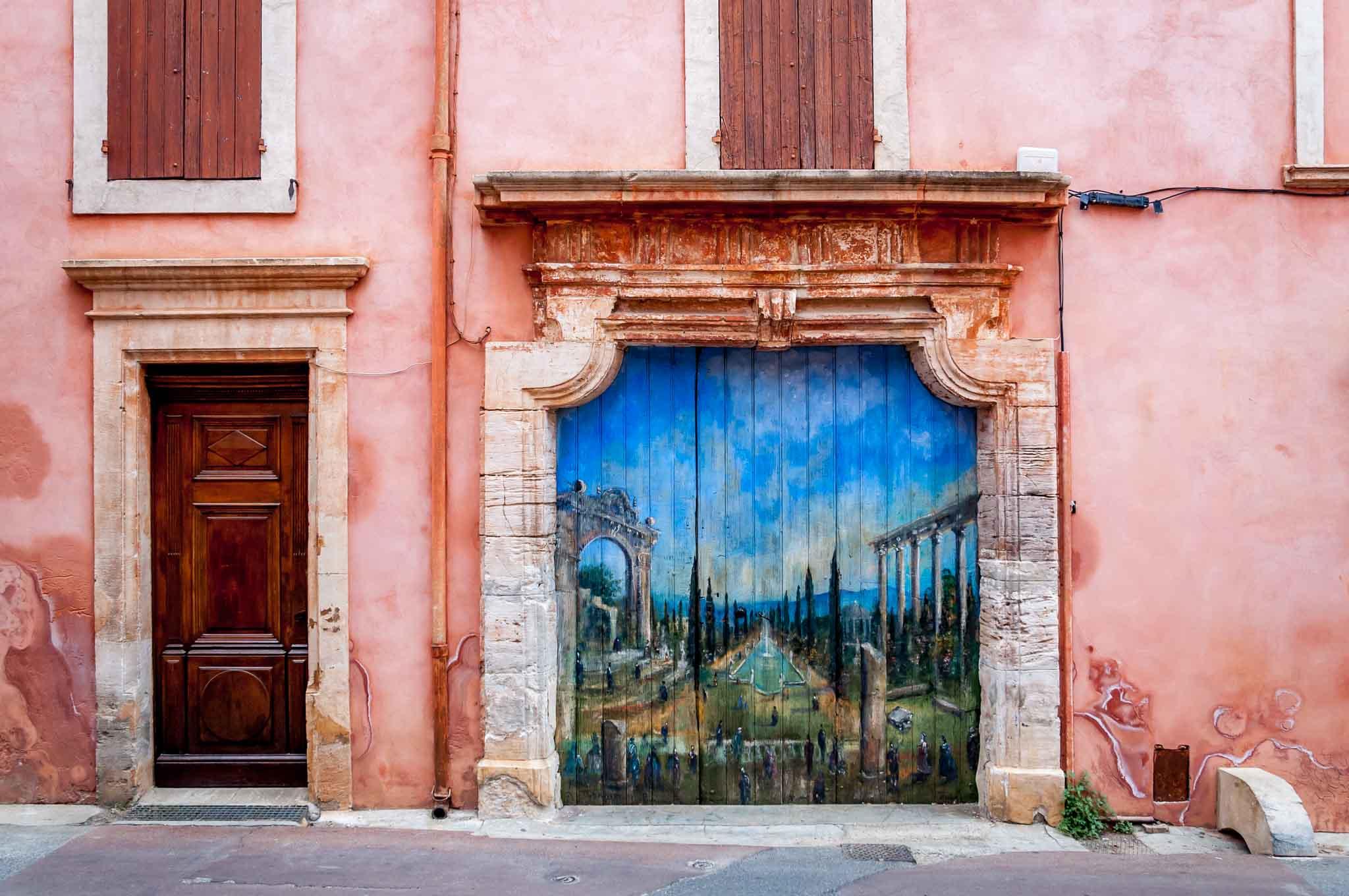 Wooden garage door painted with a scene of Roman ruins