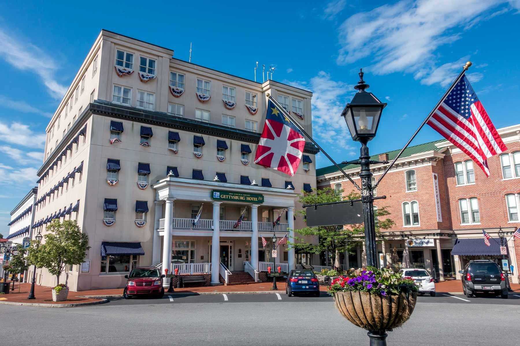 Flags flying in front of a 6-story building with rows of windows and a sign: Gettysburg Hotel