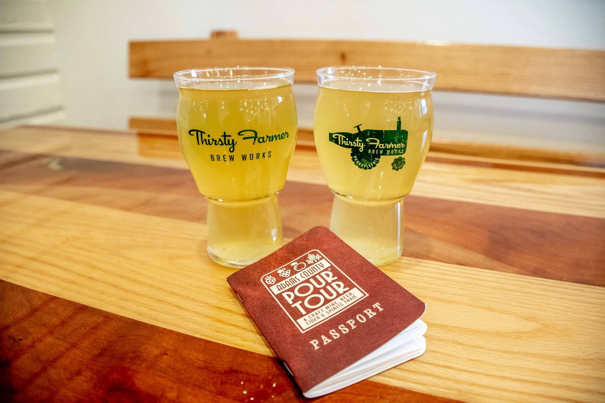 """Full beer glasses and a """"Pour Tour"""" booklet on table at the Thirsty Farmer"""