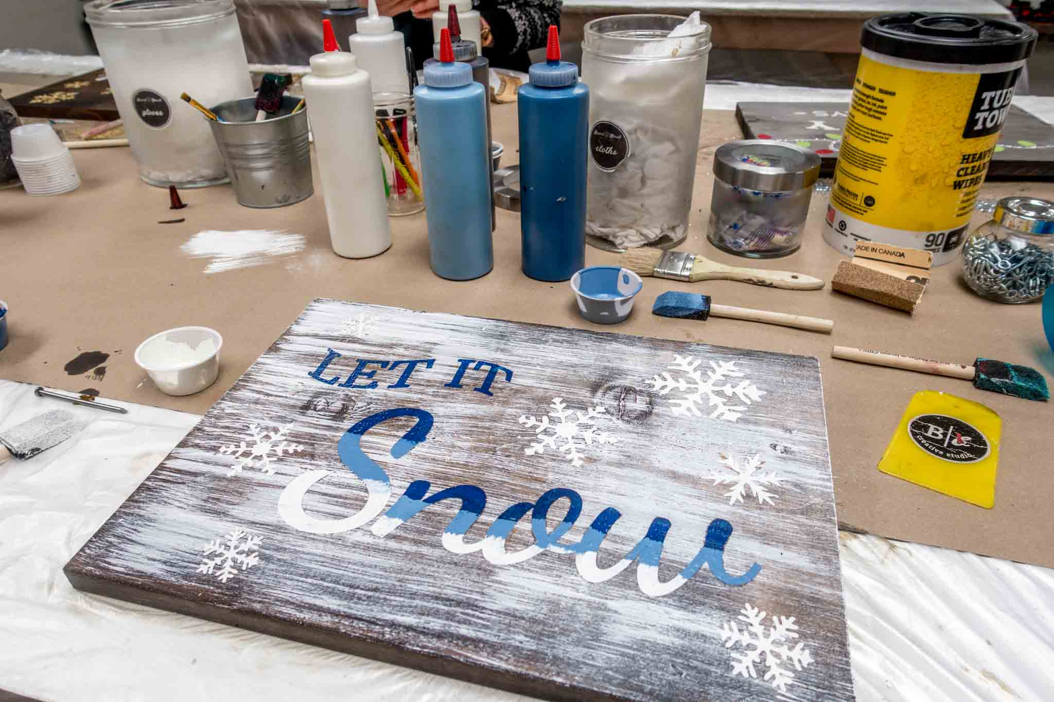Painting supplies and painted wooden sign
