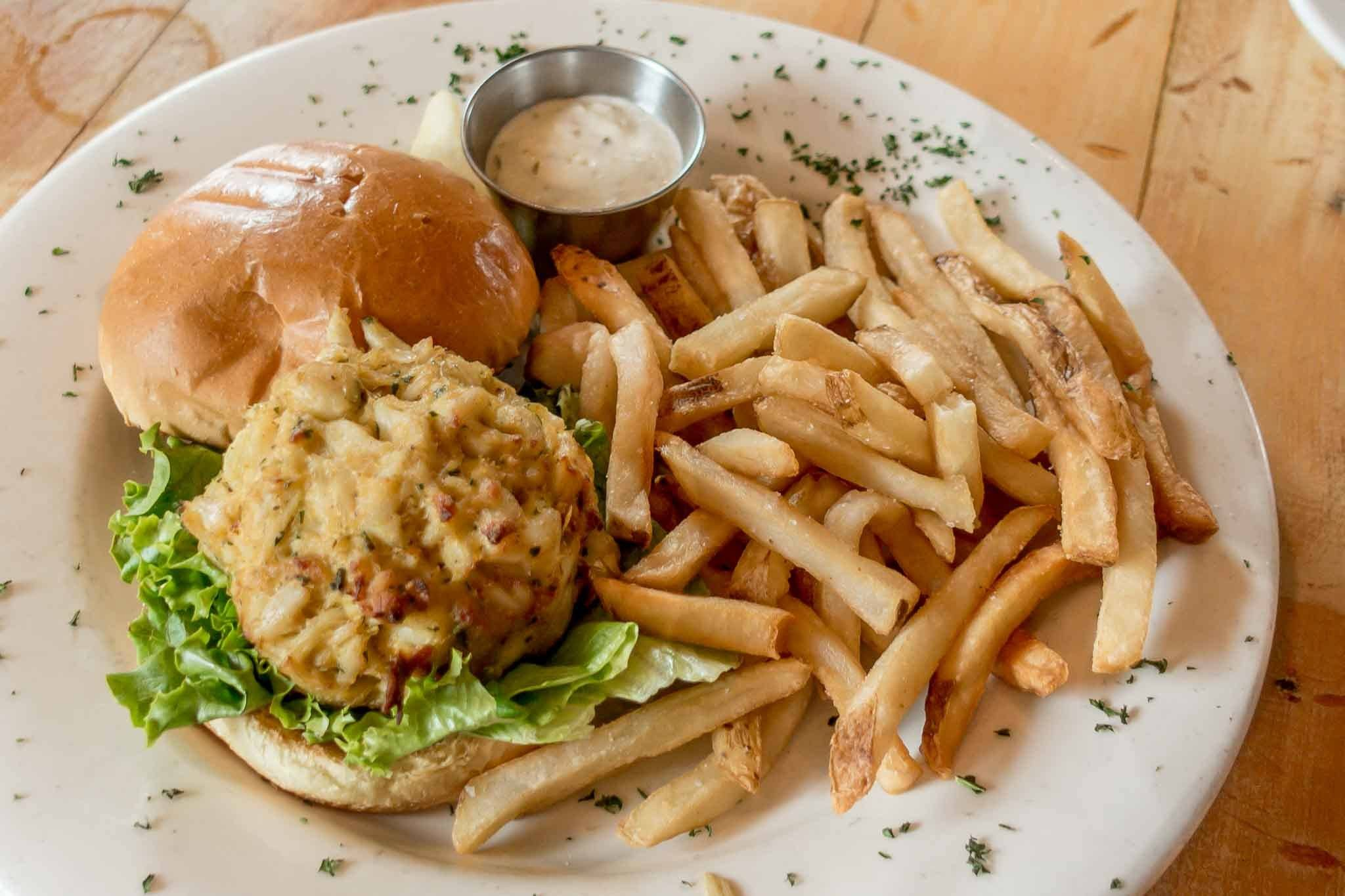 Crabcake sandwich and French fries on a plate