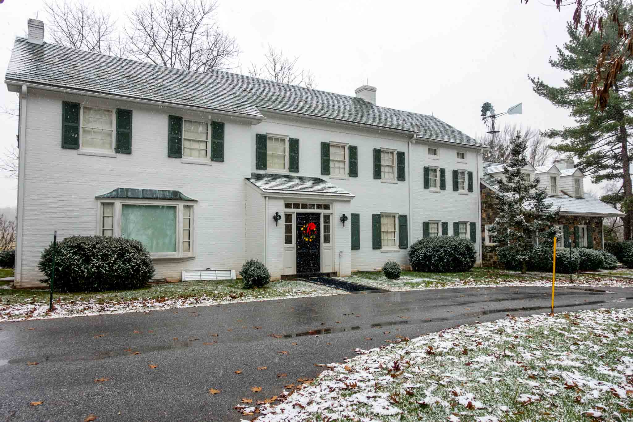 Exterior of a white brick house and snow on the ground