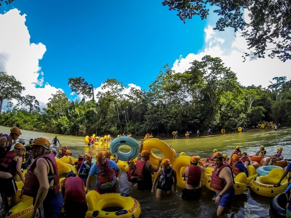 People waiting in the water with inner tubes