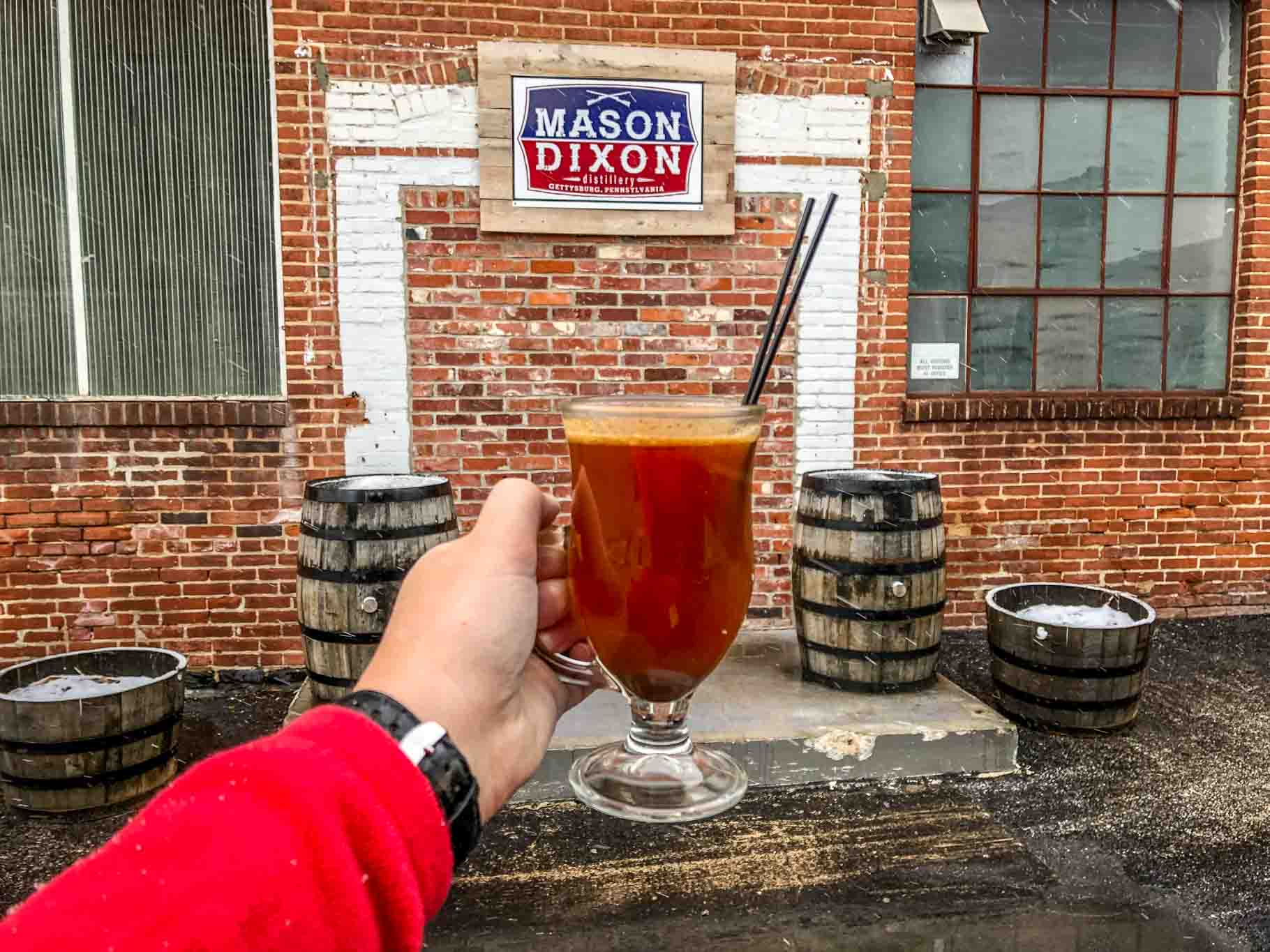 Cocktail in front of sign for Mason Dixon Distillery in Gettysburg, Pennsylvania