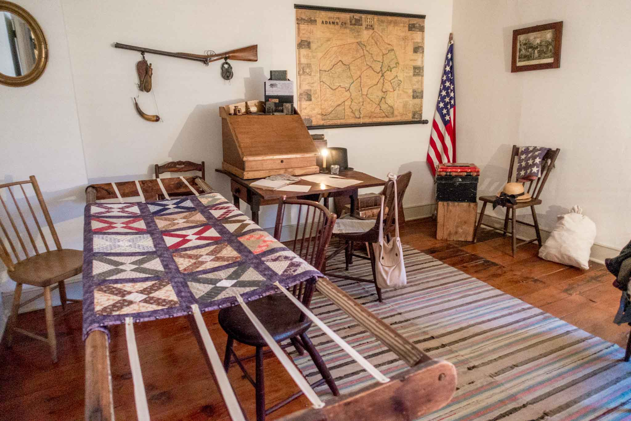 Civil War-era quilting room with desk and map