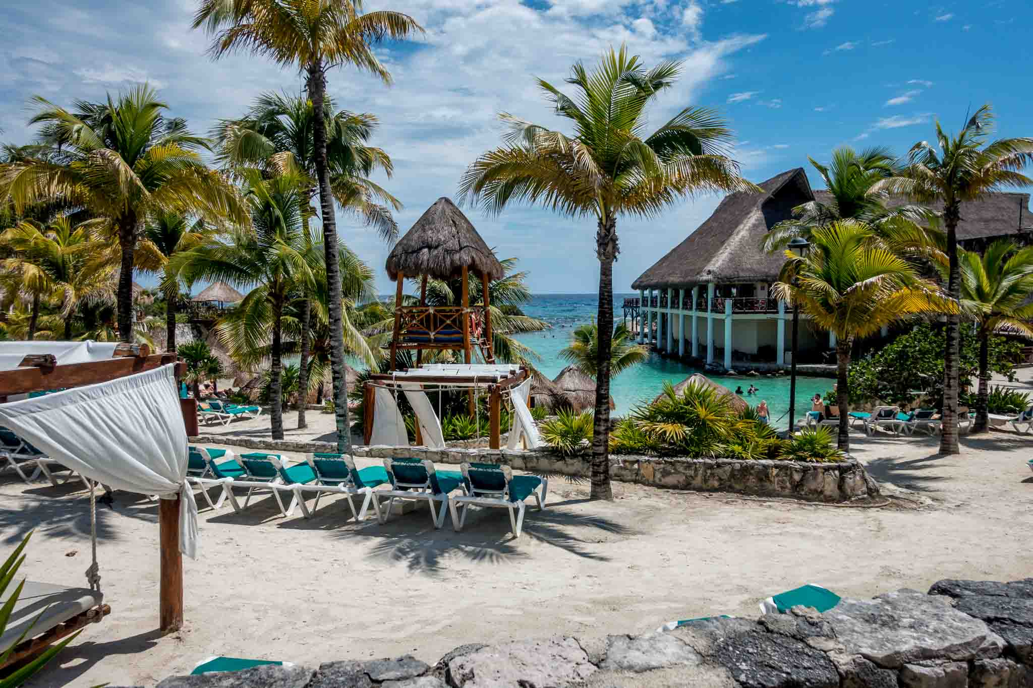 Beach area with lounge chairs and palm trees in Mexico