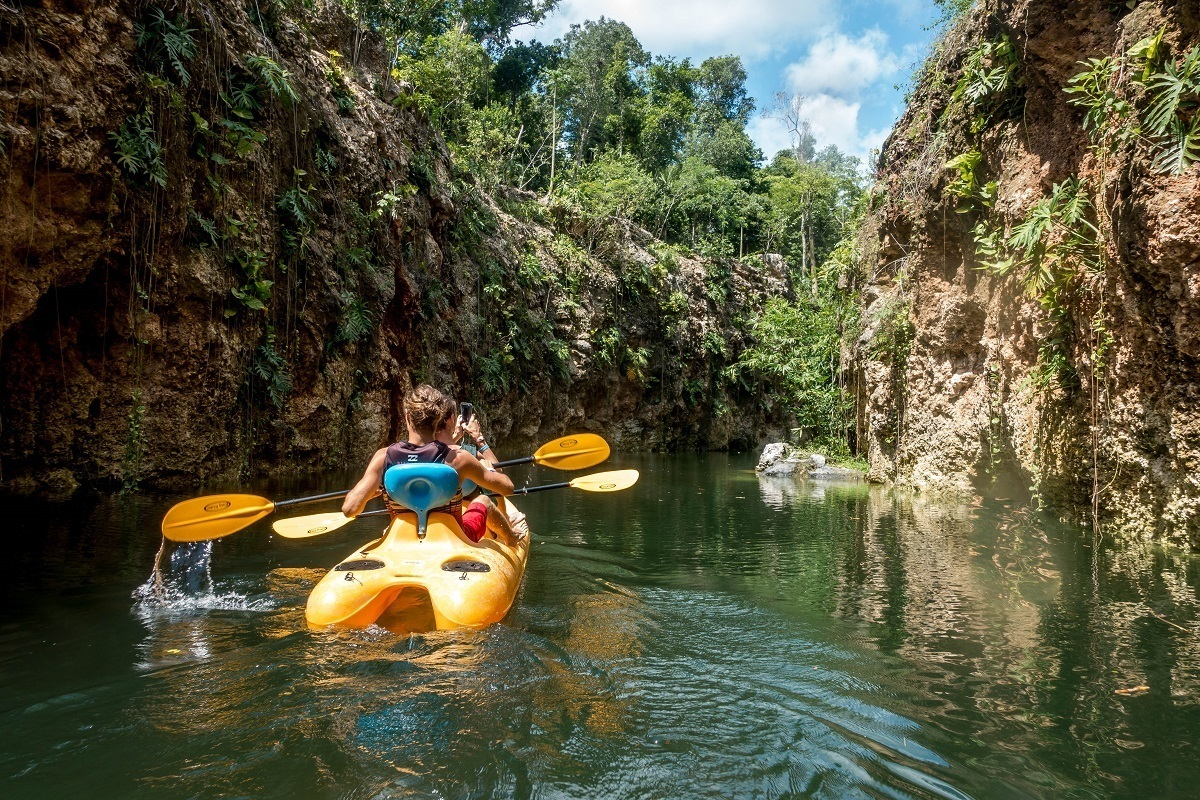 People kayaking with cliffs on both sides of the water