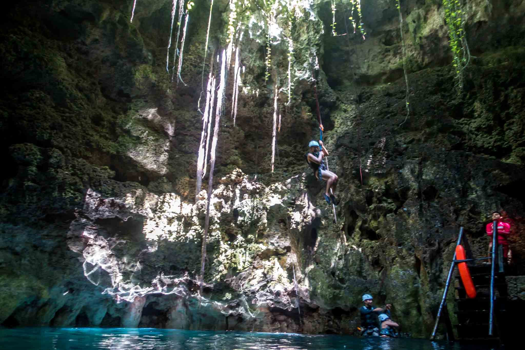People rappelling into a cave cenote near Cancun