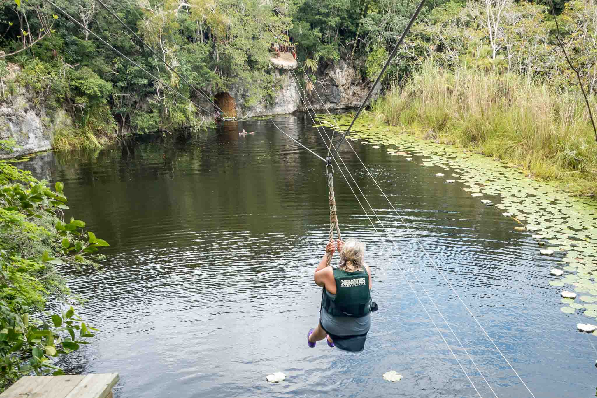 Woman zip lining into the water on a Xenotes Oasis Maya tour