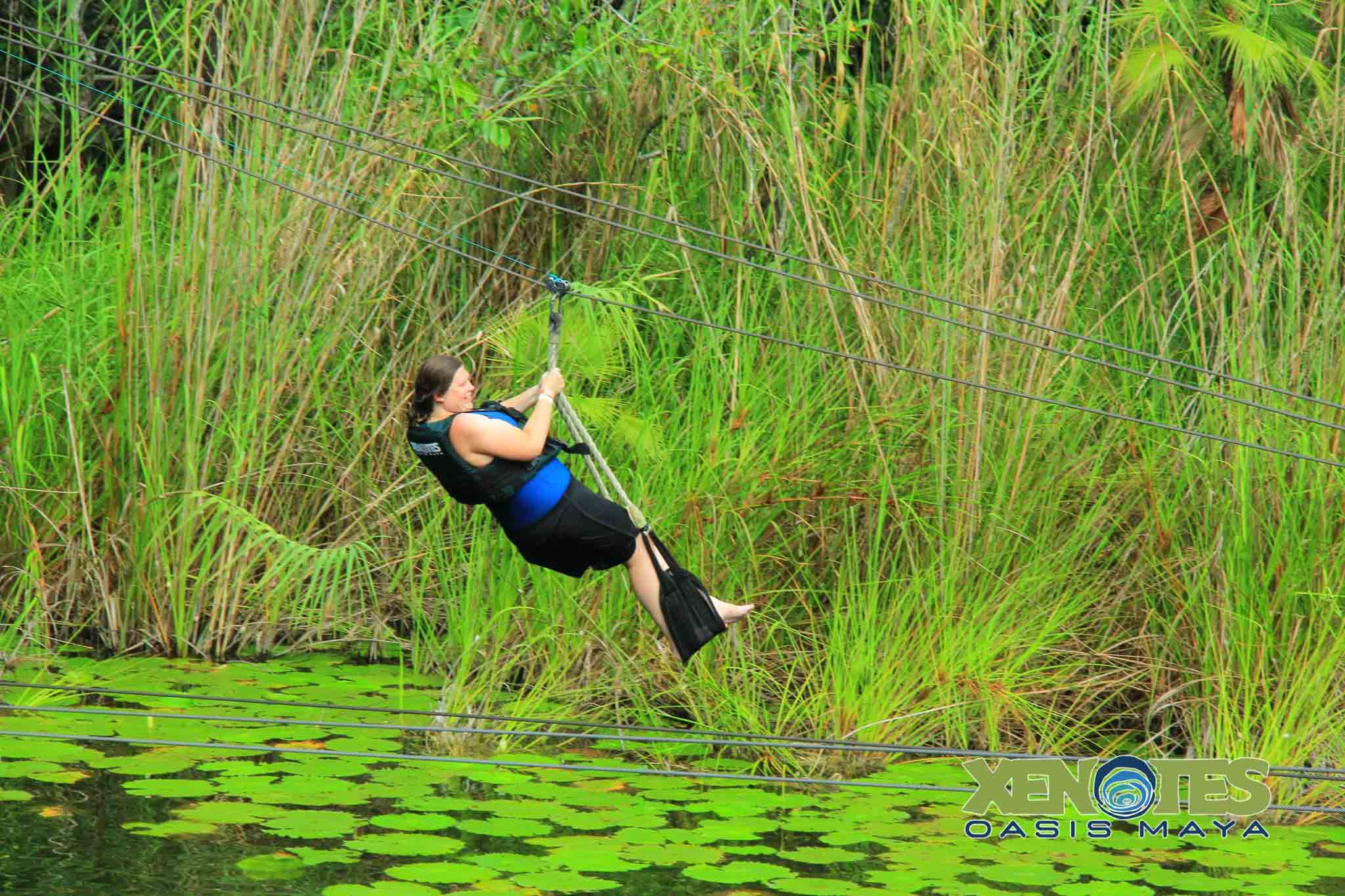 Laura on a zip line in Mexico over a cenote on a solo travel trip
