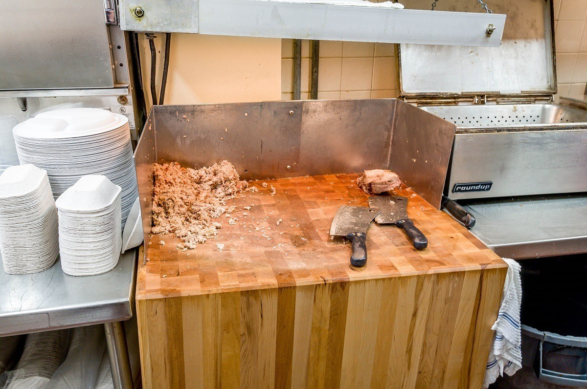 Chopped BBQ and knives on butcher block